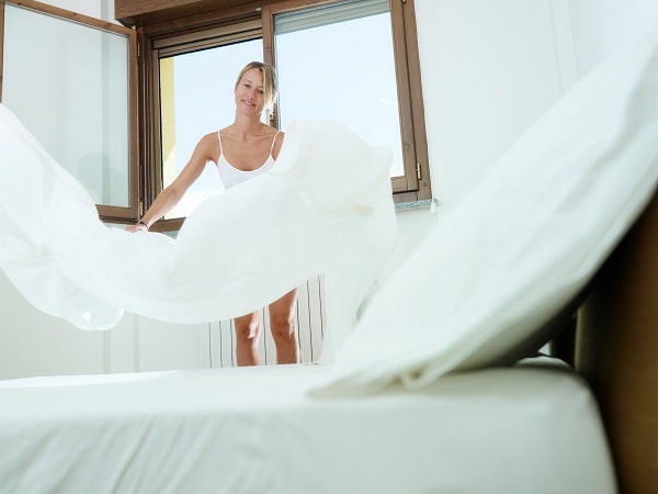 woman fluffing white sheet
