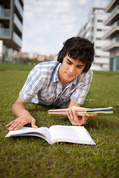 college student studying on grass