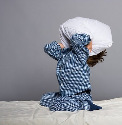 kid covering face with pillow