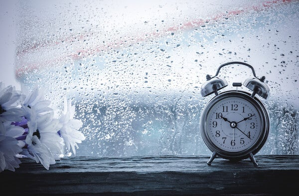 alarm clock in front of a window with rain on it