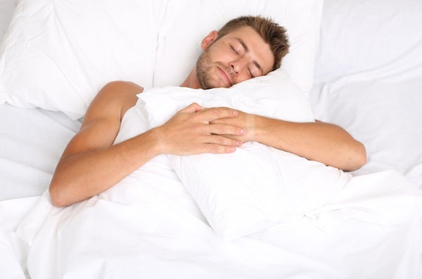 man sleeping in white bed