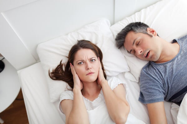 woman covering ears while man snores