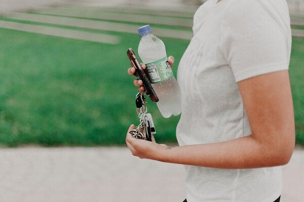 woman holding keys and bottle of water