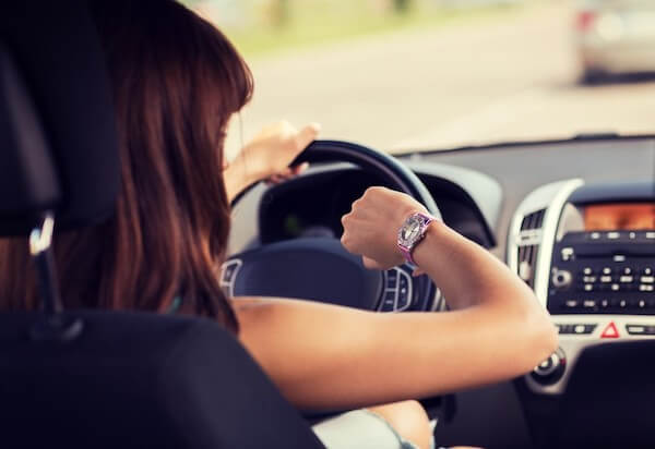 woman checking watch in car