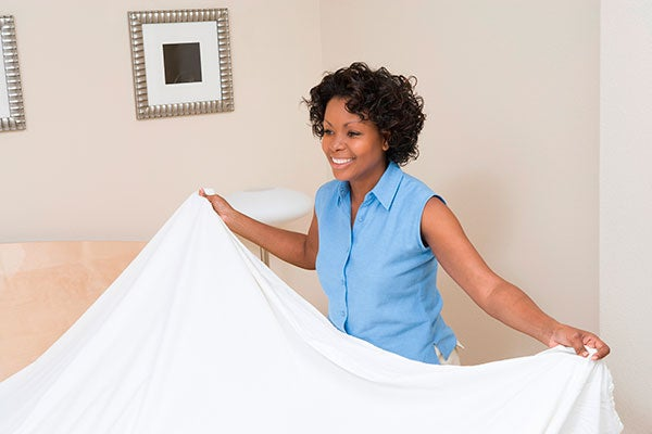 woman putting sheet on bed